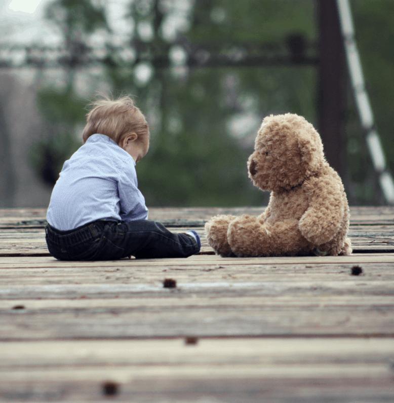 Enfant qui joue avec un ourson en peluche